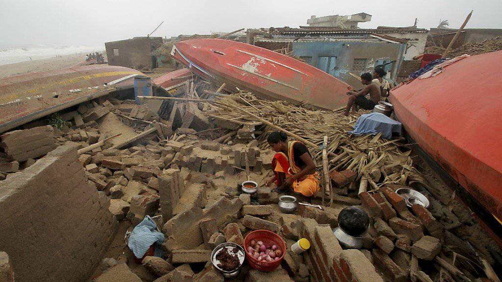 Eine Frau kocht in den Ruinen ihres zerstörten Hauses in einem Fischerdorf in Puri.