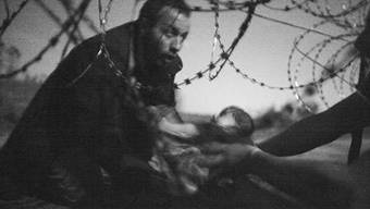 Das Sieger-Foto der World Press Photo 16 von Warren Richardson zeigt einen Flüchtling, der ein Baby unter einem Zaun hindurchreicht. Dieses und weitere prämierte Bilder sind derzeit in Zürich zu sehen.