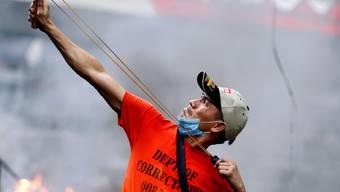 Rothemd: Ein regierungskritischer Demonstrant wehrt sich mit einer Schleuder gegen die Sicherheitskräfte.
