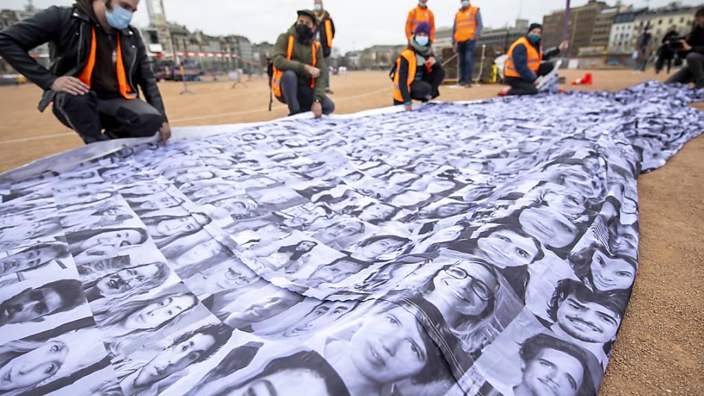 Die «We are watching»-Fahne setzt sich aus Tausenden von Porträts aus aller Welt zusamen. Quelle: KEYSTONE Fotograf: MARTIAL TREZZINI