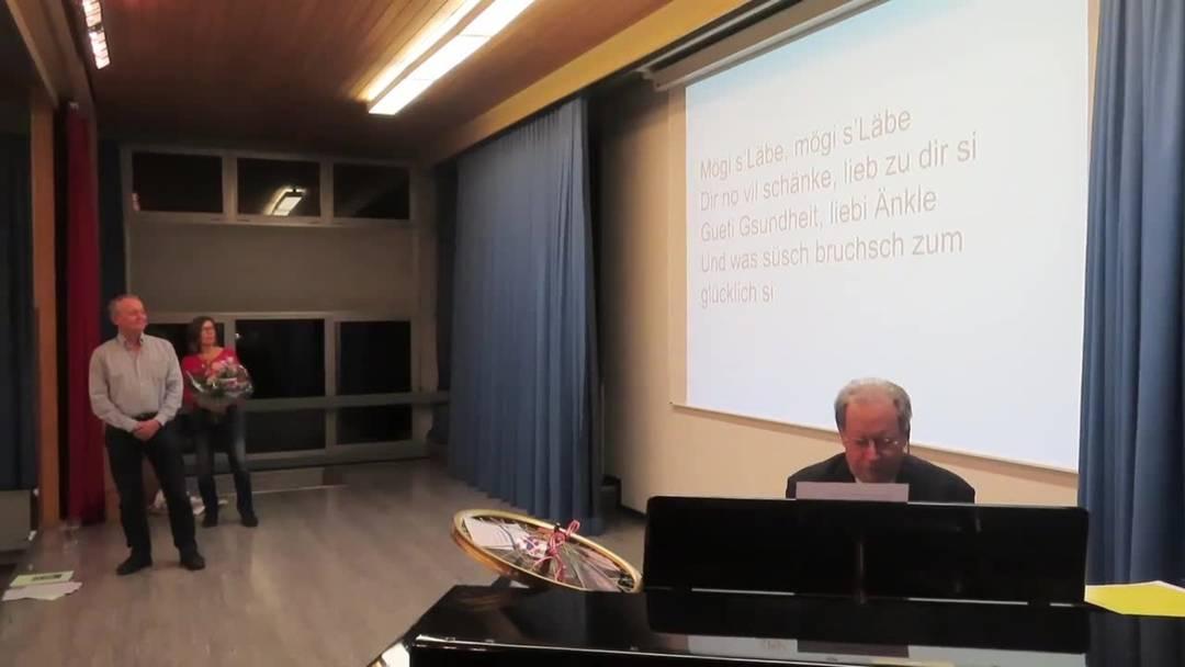 Gemeindepräsident Kuno Tschumi spielt Peter Weibel auf dem Klavier ein Abschiedslied, die ganze Gemeindeversammlung singt mit