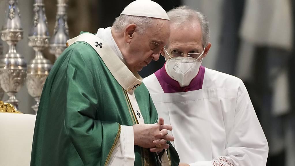 Papst Franziskus (l) spricht während eines Gottesdienst zur Eröffnung der zweijährige Weltsynode mit Guido Marini, Bischof von Tortona. Foto: Gregorio Borgia/AP/dpa