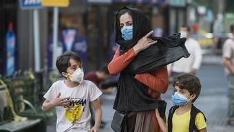 Kinder mit Gesichtsmasken gehen mit ihrer Mutter eine Straße entlang. Der Iran meldete am 21. Juli eine neue Rekordzahl an Corona-Toten. Foto: Ahmad Halabisaz/XinHua/dpa