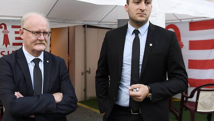 """Valentin Zuber vom Komitee """"Moutier Ville Jurassienne"""" (r.) und Pierre-André Comte vom Mouvement autonomiste jurassien sprechen vor einer Jurafahne von einem politischen Entscheid."""