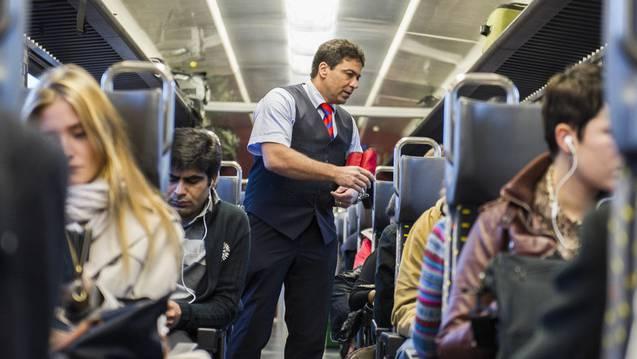 Ein Zugbegleiter kontrolliert Tickets von Passagieren. (Symbolbild)