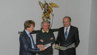Historiker Josef Kunz (l.), Bruderschaftspfleger Hans Keusch und Kirchenpflegepräsident Thomas Suter vor der Michaelsstatue in der Pfarrkirche St. Goar.