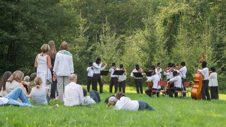 Idylle mit falschem Unterton bei der Performance von Sislej Xhafa: Das Argovia Philharmonic spielt in lauschiger Natur, sieht mit seinen Sturmmasken aber aus wie Schwerverbrecher.