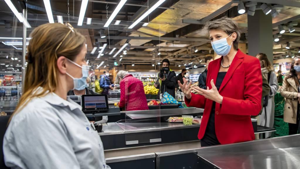 Bundesrätin Simonetta Sommaruga tauscht sich in Lausanne mit einer Verkäuferin aus.
