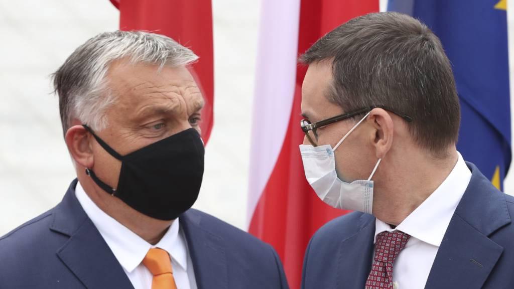 Mateusz Morawiecki (rechts), Premierminister von Polen, trägt einen Mundschutz und begrüsst Viktor Orban, Premierminister von Ungarn, ebenfalls mit Mundschutz, zum Treffen der Premierminister der Visegrad-Staaten.