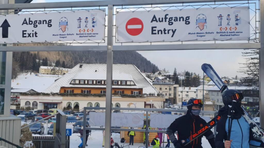 Skifahrer gehen in Semmering unter Schildern, die auf die coronabedingten Hygieneregeln hinweisen, durch. Foto: Semmering-Hirschenkogel Bergbahn/APA/dpa