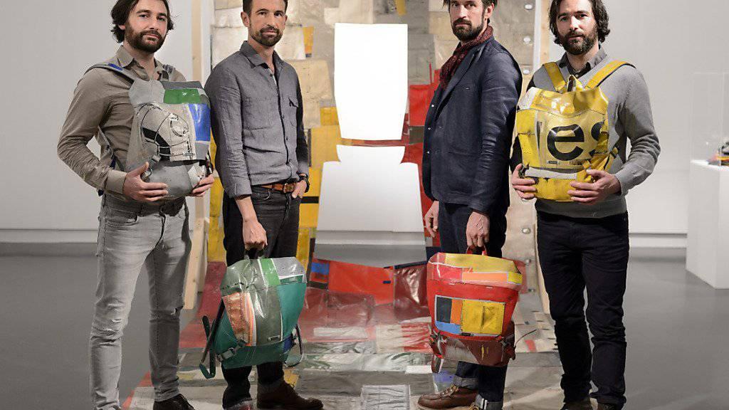 Auf der «re-recycelten» LKW-Plane zeigen Frank Riklin, Markus Freitag, Daniel Freitag und Patrik Riklin (v.l.n.r.) die Rucksäcke zum Ausleihen im Design-Museum mudac in Lausanne.