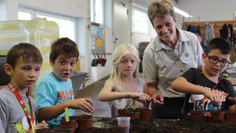 BBZ-Geschäftsleiterin Brigitte Vogel zeigt den Schülern wie Samen und Zwiebeln fachgerecht ins Pflanzentöpfli kommen.