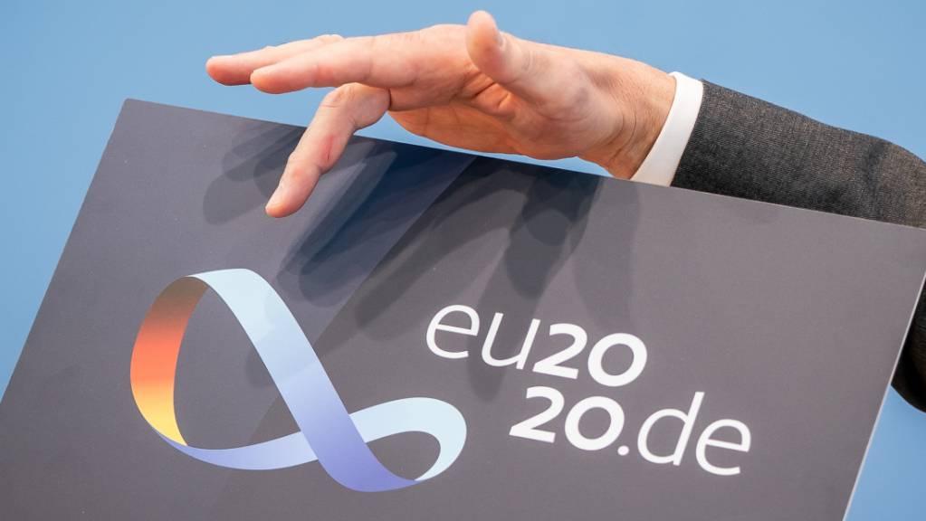 Steffen Seibert, Sprecher der Bundesregierung, zeigt das Logo der Deutschen EU-Ratspräsidentschaft. Vom 01.07. an übernimmt Deutschland die EU-Ratspräsidentschaft unter dem Motto «Gemeinsam. Europa wieder stark machen».  Im Logo ist ein Möbiusband zu sehen - ein Symbol für Einigkeit und Verbundenheit. Foto: Michael Kappeler/dpa