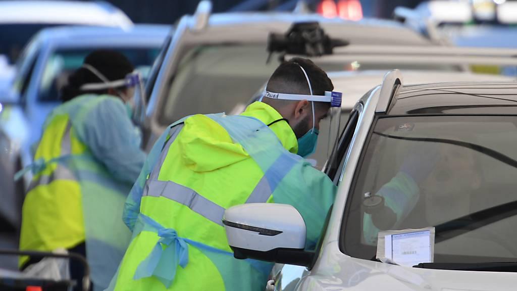Autos stehen Schlange, um sich am Bondi Beach auf das Coronavirus testen zu lassen. Teile der australischen Metropole Sydney gehen nach mehreren Dutzend Corona-Neuinfektionen in einen strikten Lockdown. Foto: Dean Lewins/AAP IMAGE/dpa