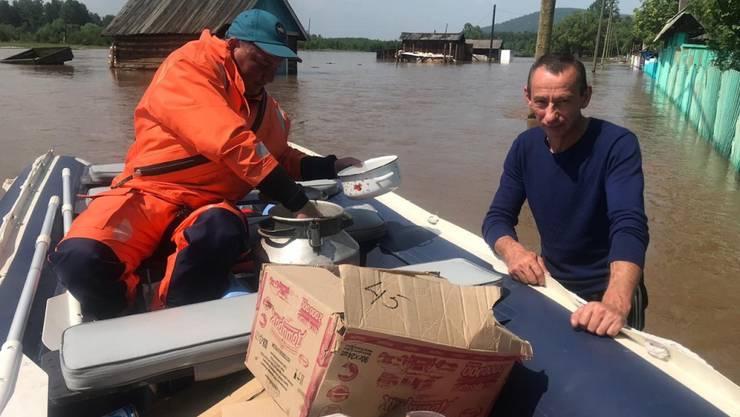 Nothelfer bringen den Menschen in den vom Hochwasser betroffenen Gebieten Lebensmittel.