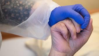 Eine Altenpflegerin in Schutzausrüstung hält die Hand eines Bewohners. Foto: Sebastian Gollnow/dpa