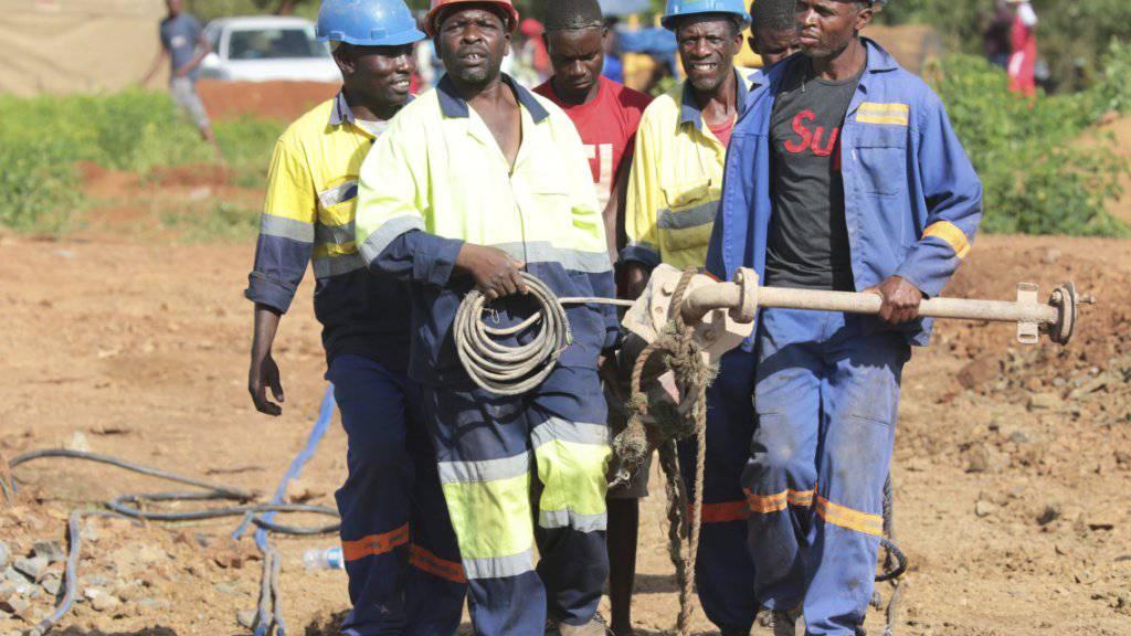Minenarbeiter mit schwerem Gerät auf dem Weg zur überfluteten Goldmine in Simbabwe, in der dutzende illegal tätige Goldschürfer ums Leben gekommen sein dürften.