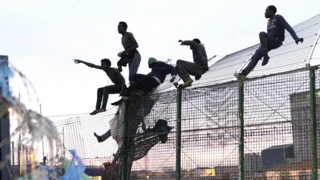 Migranten klettern über den Grenzzaun in Spaniens Enklave Melilla