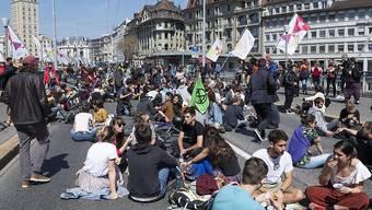 Klimaaktivisten haben sich am Donnerstag in Lausanne mitten auf die Fahrbahn der Grand-Pont-Brücke gesetzt, um ihr Mittagessen einzunehmen und gegen die Umweltzerstörung zu protestieren.