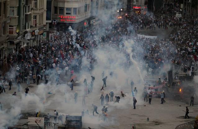 Polizisten werfen Tränengas-Granaten Richtung Demonstranten