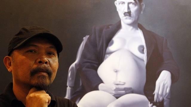 Hitler mit Schwangerschaftsbauch: Der Indonesische Künstler Ronald Manullang vor seinem Werk