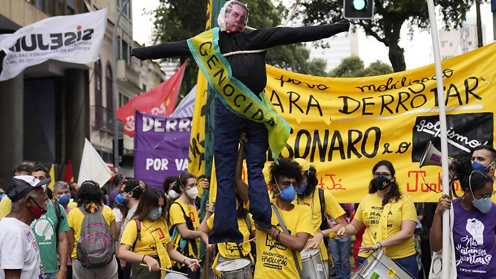 Ein Demonstrant hält ein Bildnis des brasilianischen Präsidenten Bolsonaro, auf dem «Völkermörder» zu lesen ist, während einer Demonstration am Unabhängigkeitstag in Rio de Janeiro gegen den Umgang des Präsidenten mit der Corona-Pandemie, der Wirtschaft und der Korruption. Foto: Silvia Izquierdo/AP/dpa