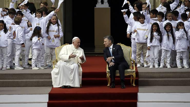 Papst Franziskus und Kolumbiens Präsident Juan Manuel Santos unterhalten sich vor einer Zeremonie.