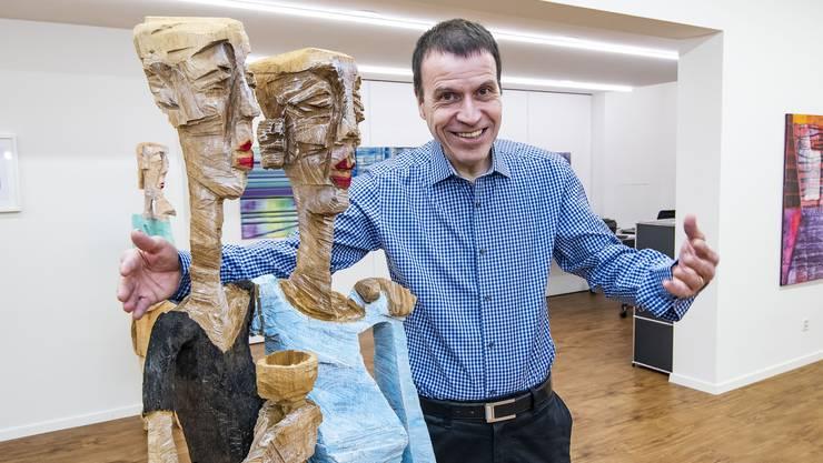 Alexander Sarasin posiert in seiner Galerie mit einer Skulptur des Baselbieter Künstlers Thomas Ruepp.
