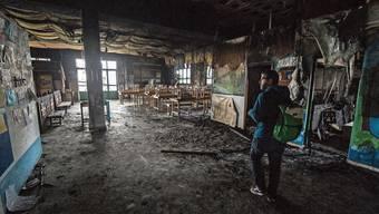 Ein Schweizer Flüchtlingshelfer sieht sich an, was von der Schule auf Lesbos übrig geblieben ist.