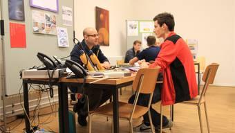 Ein Schüler bespricht sein Bewerbungsdossier mit einem Firmenvertreter.pah