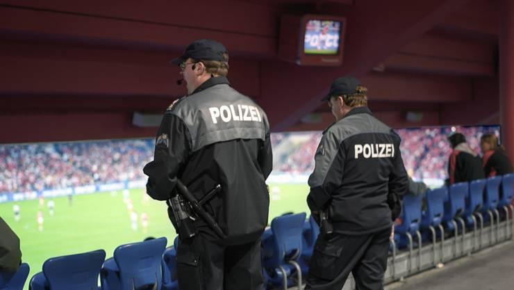 Zwei Polizisten beobachten im St. Jakob Park in Basel das Geschehen auf der Tribüne und auf dem Spielfeld.