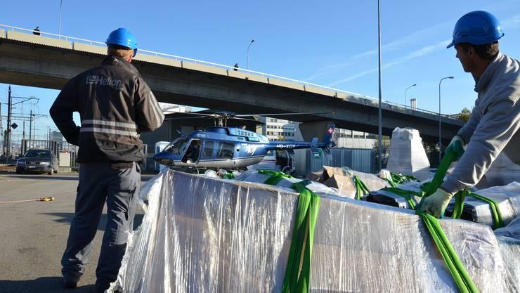 1. Am Boden werden die Bauteile für die Photovoltaikanlage auf dem Dach des Briefzentrums Mülligen an einem Lastseil befestigt