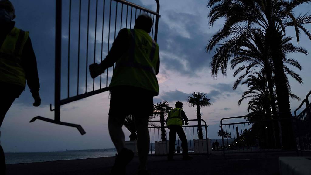 dpatopbilder - Ein Angestellter der Stadt Nizza trägt einen Absperrzaun, um die Promenade des Anglais am Vorabend der coronabedingten Wochenendabriegelung für die Öffentlichkeit abzusperren. Foto: Valery Hache/AFP/dpa
