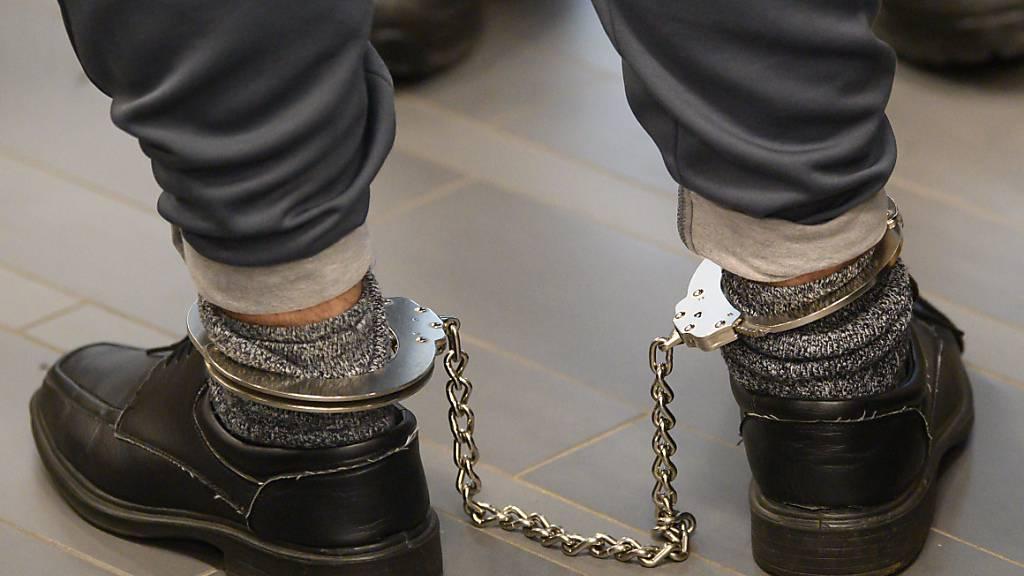 Ein Angeklagter steht vor der Urteilsverkündung mit Fußfesseln im Verhandlungssaal des Oberlandesgerichts in Dresden. Nach der tödlichen Messerattacke auf zwei Touristen in Dresden ist der 21-Jährige zu lebenslanger Freiheitsstrafe verurteilt worden. Foto: Robert Michael/dpa-Zentralbild Pool/dpa