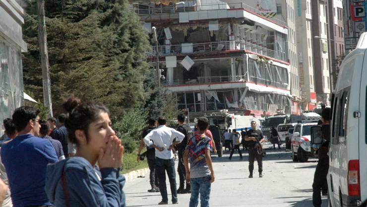 Passanten und Sicherheitskräfte stehen vor dem Provinzbüro der türkischen Regierungspartei AKP in der Stadt Van, das bei einem Autobombenanschlag stark beschädigt wurde.