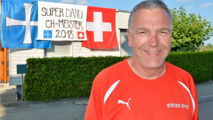 Schweizer Meister Daniel Büttiker vor seinem beflaggten Haus.
