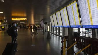 Ein Reisender, der als vorbeugende Maßnahme gegen die Verbreitung des Coronavirus eine Mund-Nasen-bedeckung trägt, schaut auf die Anzeigetafeln mit den Abflügen am Flughafen Schiphol bei Amsterdam. Foto: Peter Dejong/AP/dpa