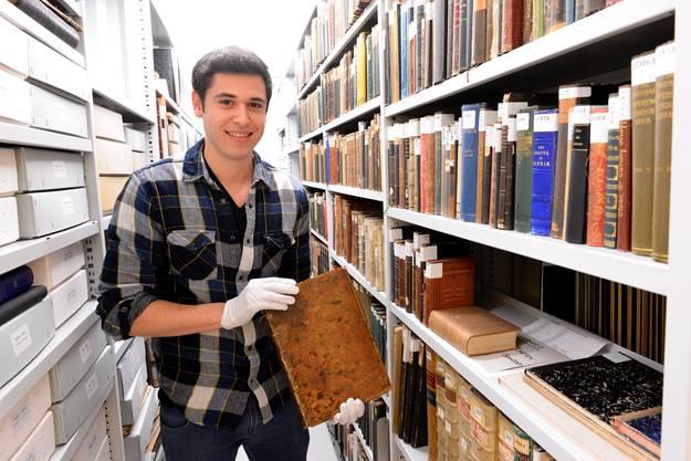Er hat das 450-jährige Buch aus dem Archiv der Mission 21 geholt.