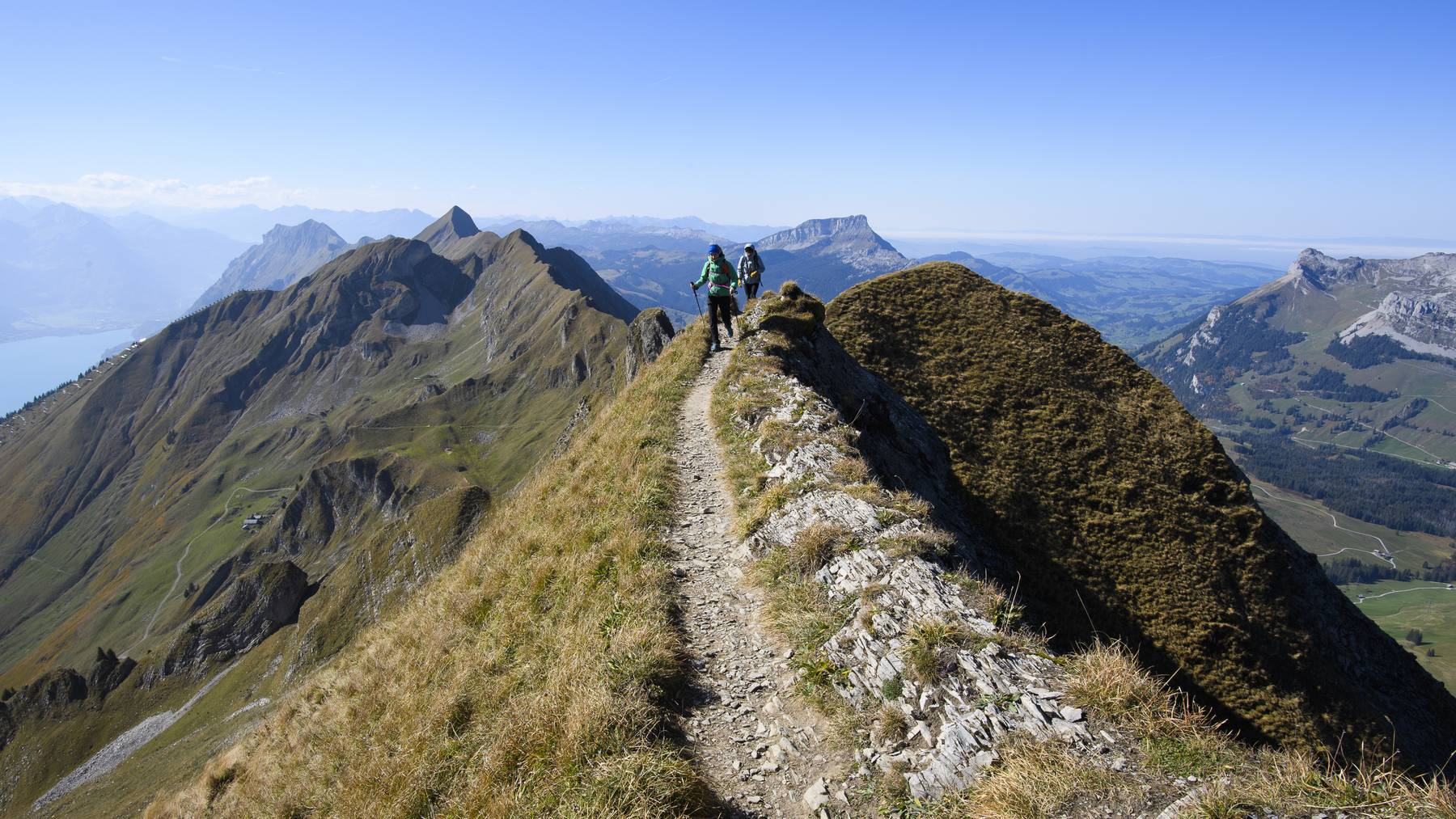 Two women walk on the Brienzer Rothorn Mountain, 2350 meters above sea level, in the Bernese Alps on the boundary between the Cantons of Berne and Lucerne, Switzerland, on Wednesday, October 10, 2018.