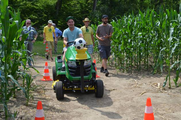 Regierungsrat Markus Dieth besucht in Wettingen die dritte Ausgabe des Maislabyrinths: Andreas Benz fährt den Rasenmäher-Parcours ab.