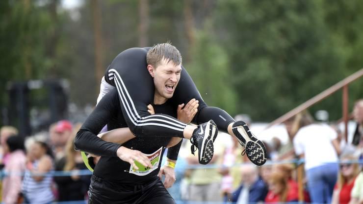 Die Weltmeisterschaft findet seit 1992 in Sonkajärvi statt. Beim Wettkampf muss ein Mann eine Frau huckepack oder kopfüber getragen. Hier im Bild: Jukka Ohtonen und Jonna Alho aus Finnland.