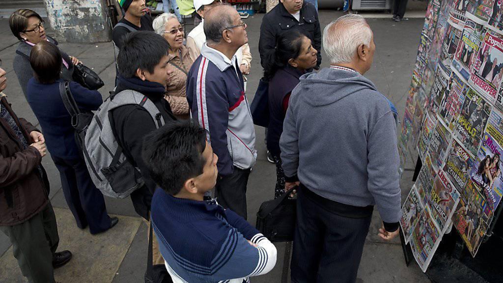 Passanten lesen die Schlagzeilen der Zeitungen nach der Präsidentenwahl in Peru. Das Rennen bleibt eng, noch steht kein Sieger fest.