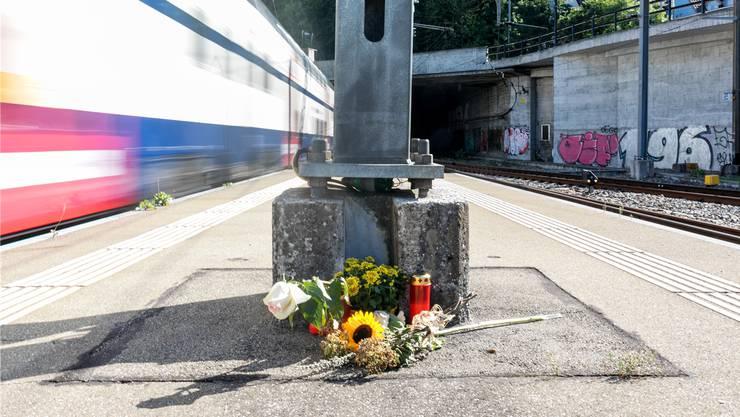 Blumen und Kerzen erinnern am Bahnhof Baden an den tödlichen Unfall:Hier wurde in der Nacht auf Sonntag ein SBB-Kundenbegleiter eingeklemmt und mitgeschleppt.