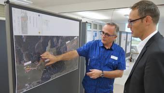 Franco Castelanelli, Projektleiter neue Energien bei den CKW (links), und David Gautschi, Leiter Erneuerbare Energie bei der AEW Energie AG betrachten auf der Luftaufnahme die genauen Standorte der vier Windkraftanlagen.