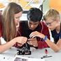 Anja Hinder unterstützt die Kinder dabei, dem «Me-Arm» die Arme korrekt anzubringen.
