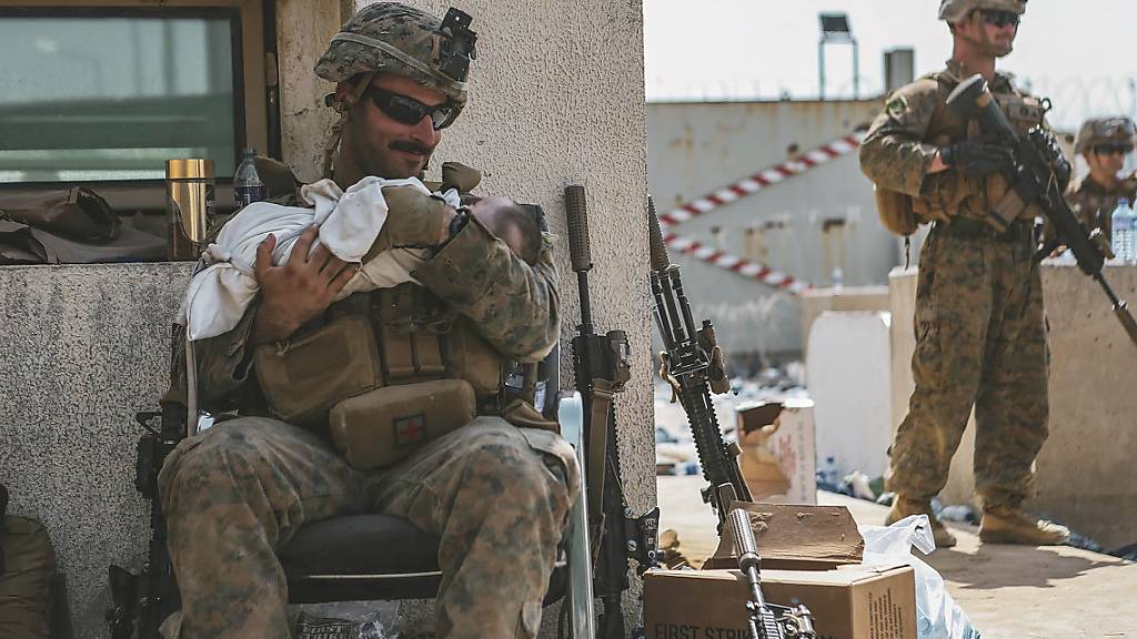 dpatopbilder - HANDOUT - Viele Eltern und viele Babys suchen Schutz am Flughafen in Kabul. In diesem vom US Marine Corps zur Verfügung gestellten Foto beruhigt ein US-Marine ein Kleinkind. Foto: Sgt. Isaiah Campbell/U.S. Marine Corps/AP/dpa - ACHTUNG: Nur zur redaktionellen Verwendung im Zusammenhang mit der aktuellen Berichterstattung und nur mit vollständiger Nennung des vorstehenden Credits