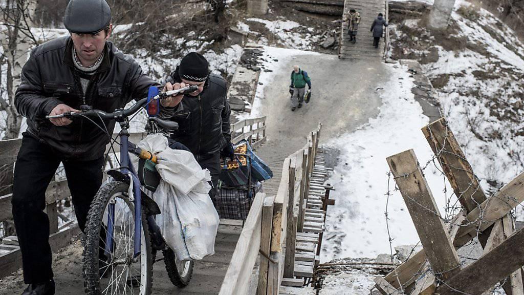 Ostukrainer gehen über eine improvisierte Brücke in der Nähe von Luhansk. Der Konflikt in der Ostukraine belastet den Alltag der Einwohner immer noch stark, laut der UNO. (Archiv)