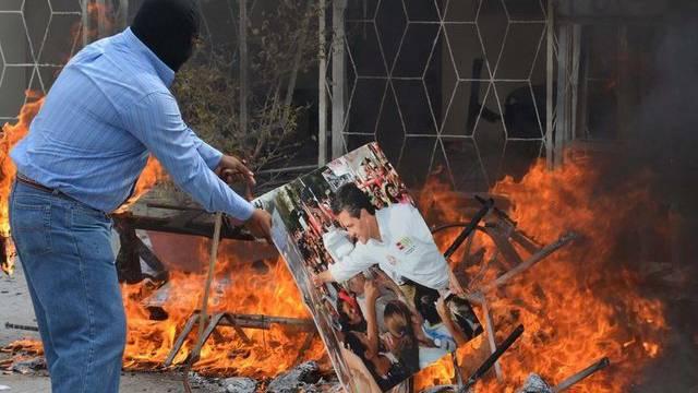 Ein Demonstrant in Mexiko verbrennt das Bild von Präsident Nieto