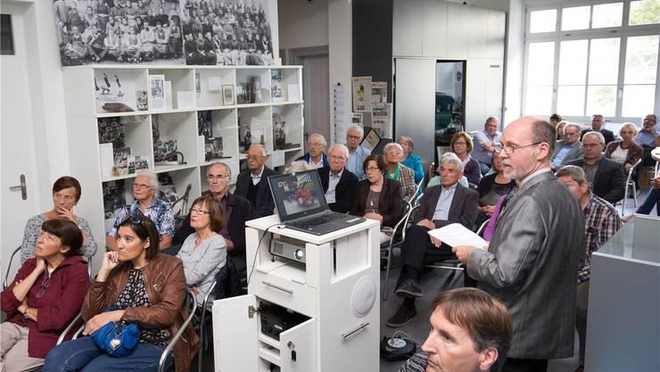 Finissage der grossen Sonderausstellung Brandspuren: Projektleiter Josef C. Haefely (stehend) lässt die Höhepunkte des vergangenen Museumsjahres in einemBilderbogen nochmals aufleben.