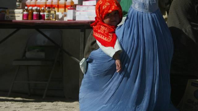 Eine Afghanin wartet mit ihrem Kind auf medizinische Hilfe (Archiv)